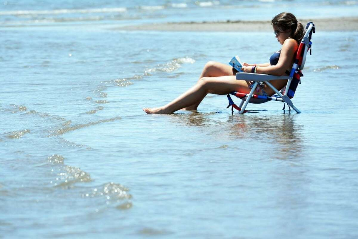 Jackie Turiano, of Shelton, enjoys a book while keeping her feet cool in the waters of Long Island Sound at Seaside Park, in Bridgeport, Conn. July 27, 2016.