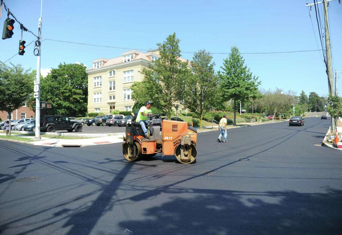 Construction workers pave a stretch of Mason Street in Greenwich, Conn. Tuesday, Aug. 1, 2017. Re-paving work on along Milbank Avenue and Mason Street has caused recent road closures and the drainage project near the YMCA on East Putnam Avenue will restrict traffic to one lane in each direction beginning this week.