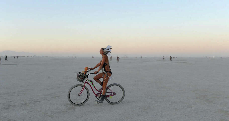 A woman rides a bicycle on the playa after sunset at the Burning Man festival in this file photo from Gerlach, Nev. on Friday, Aug. 30, 2013. Thousands of bicycles were abandoned by Burners in 2017, and groups are looking to make sure the bikes make its way to hurricane victims. Photo: Andy Barron, ASSOCIATED PRESS / AP2013
