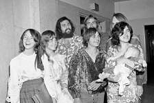 """Members of Charles Manson's """"family"""" congregate in Los Angeles Hall of Justice, Feb. 24, 1970,  for arraignment of Patricia Krenwinkel, a defendant in the Sharon Tate murder case. None of these is accused.  From left: Lynette """"Squeaky"""" Fromme, Sandra Good, Mark Ross, Paul Watkins and  Catherine """"Gypsy"""" Share holding Catherine Good's son Ivan.  Two men partially hidden in back are unidentified. (AP Photo/Wally Fong)"""