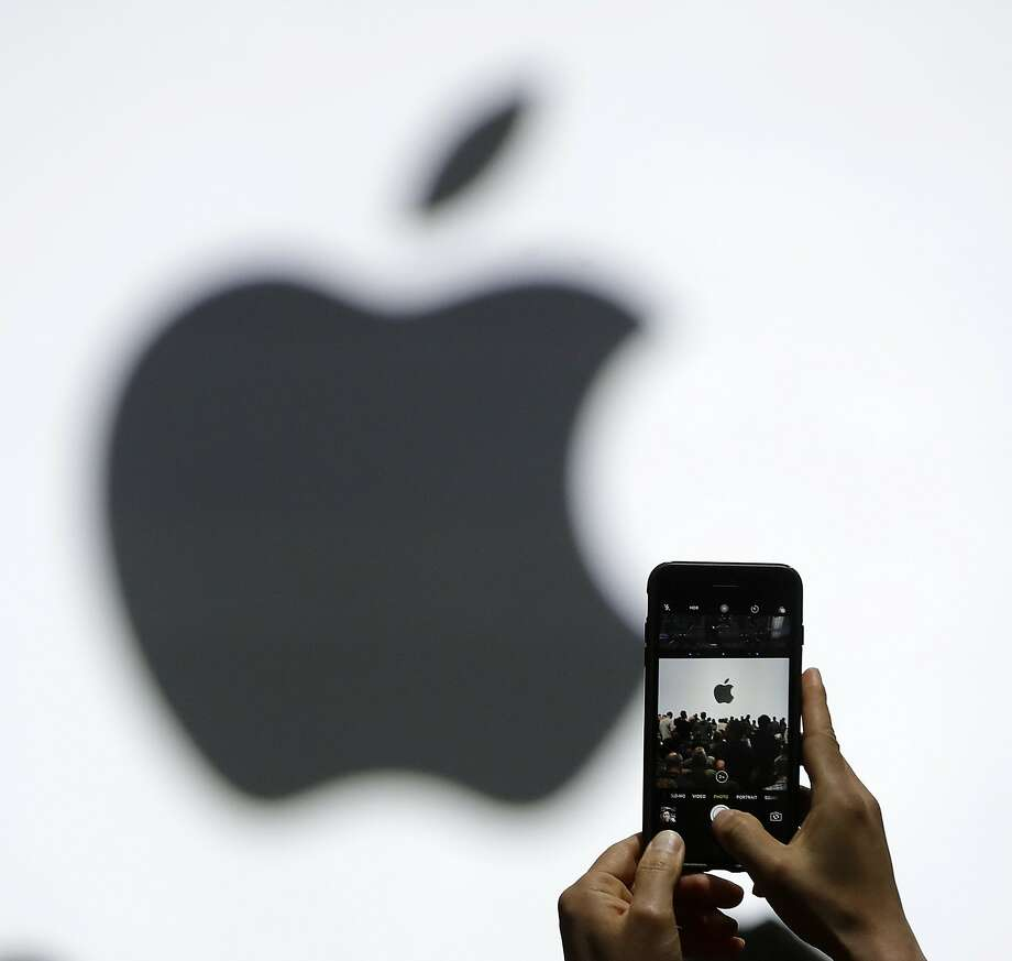FILE - In this Monday, June 5, 2017, file photo, a person takes a photo of an Apple logo before an announcement of new products at the Apple Worldwide Developers Conference in San Jose, Calif. Apple is getting ready to use iPhone cameras as an entryway into the strange world of augmented reality, taking the trend-setting company down an avenue that could usher in a new era in technology. (AP Photo/Marcio Jose Sanchez, File) Photo: Marcio Jose Sanchez, Associated Press