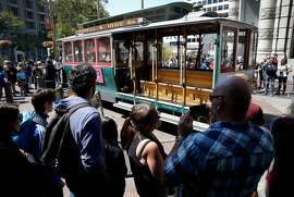 Passengers wait in line for up to an hour to board cable cars at the turnaround at Powell and Market streets in San Francisco, Calif. on Tuesday, Aug. 1, 2017. A controller's report released this week found that many fares went uncollected by conductors from passengers wanting to pay with cash on board.