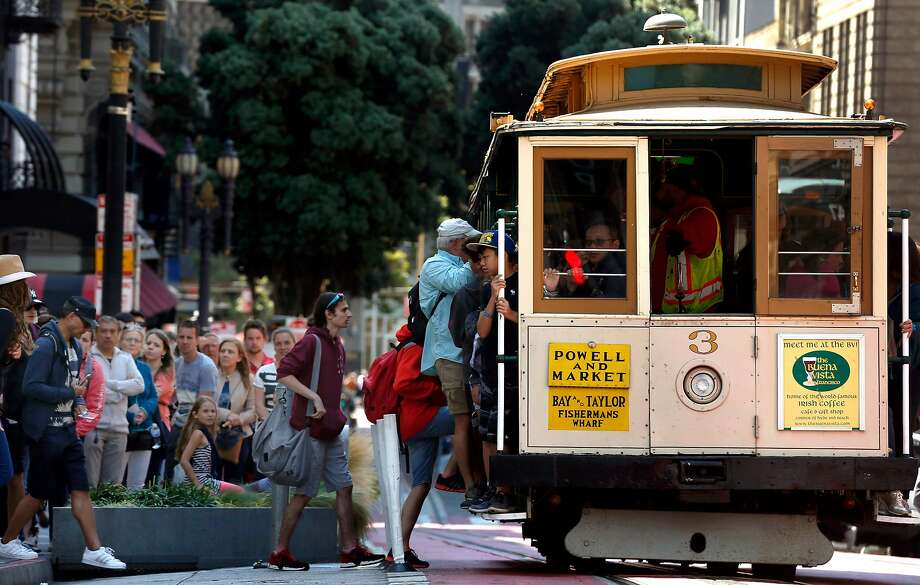 Passengers wait in line to board a cable car at Powell and O'Farrell streets in San Francisco. Photo: Paul Chinn, The Chronicle