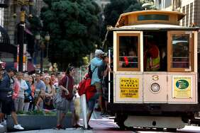 Passengers wait in line to board a cable car at Powell and O'Farrell streets in San Francisco.