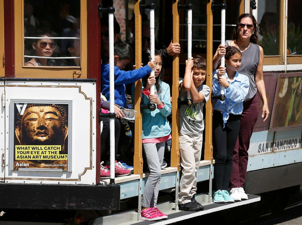Passengers hang on as a cable car rolls down Powell Street towards the end of the line at Market Street in San Francisco. Two cable car lines share Powell street: the Powell-Hyde line and the Powell-Mason line.