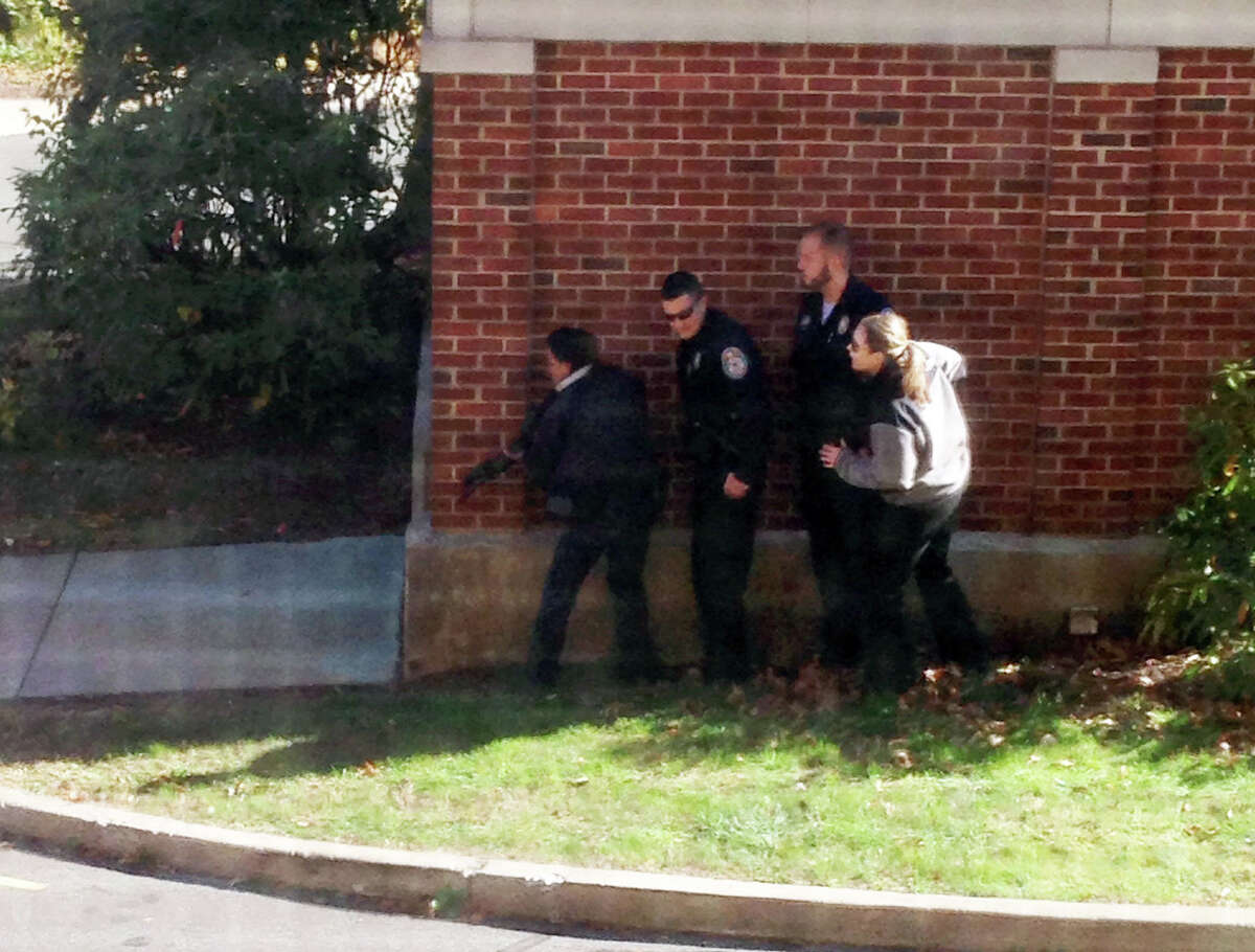 In this photo taken through a window and provided to the AP, which has been authenticated based on its contents and other AP reporting, police officers respond to a report of a suspicious person at Central Connecticut State University in New Britain, Conn., Monday, Nov. 4, 2013, The campus was locked down Monday and students were urged to remain indoors and away from windows. (AP Photo/Kiara Gupton via WFSB)