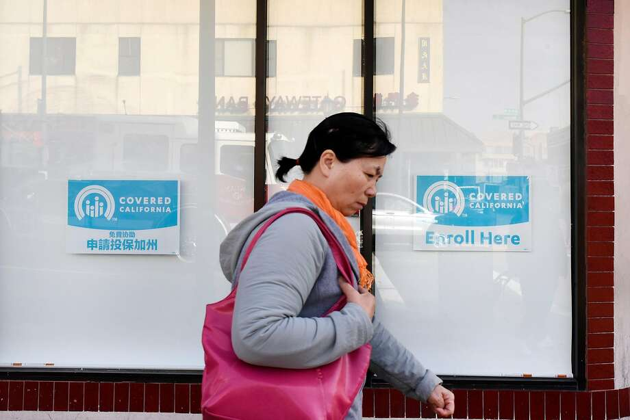 Pedestrians walk past signs for Covered California in the windows of the Asian Health Services offices in January. Roughly 1.3 million Californians are enrolled in plans through the exchange. Photo: Michael Short, Special To The Chronicle