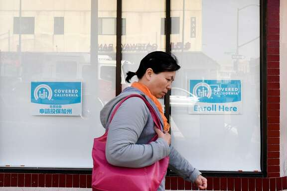 Pedestrians walk past signs for Covered California in the windows of the Asian Health Services offices on the final day of open enrollment for Covered California, the state's health insurance marketplace created by the Affordable Care Act, in Oakland, CA on Tuesday, January 31, 2017.