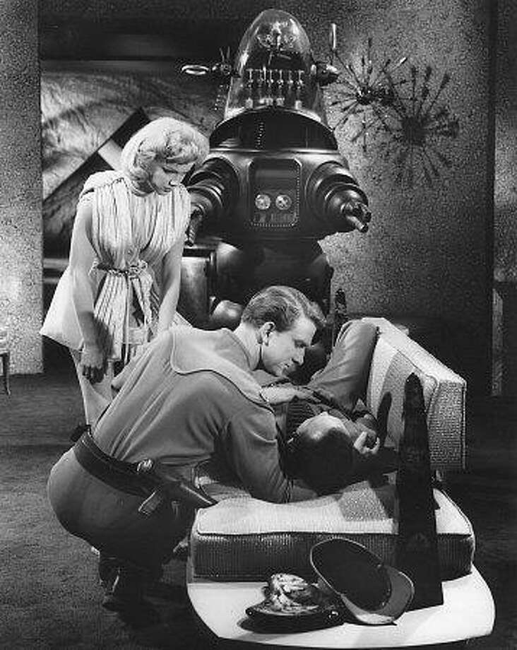 Leslie Nielsen, Ann Francis and Robbie the Robot star in the 1956 science fiction classic Forbidden Planet.  credit: photo courtesy of Leslie Nielsen. emailed photo