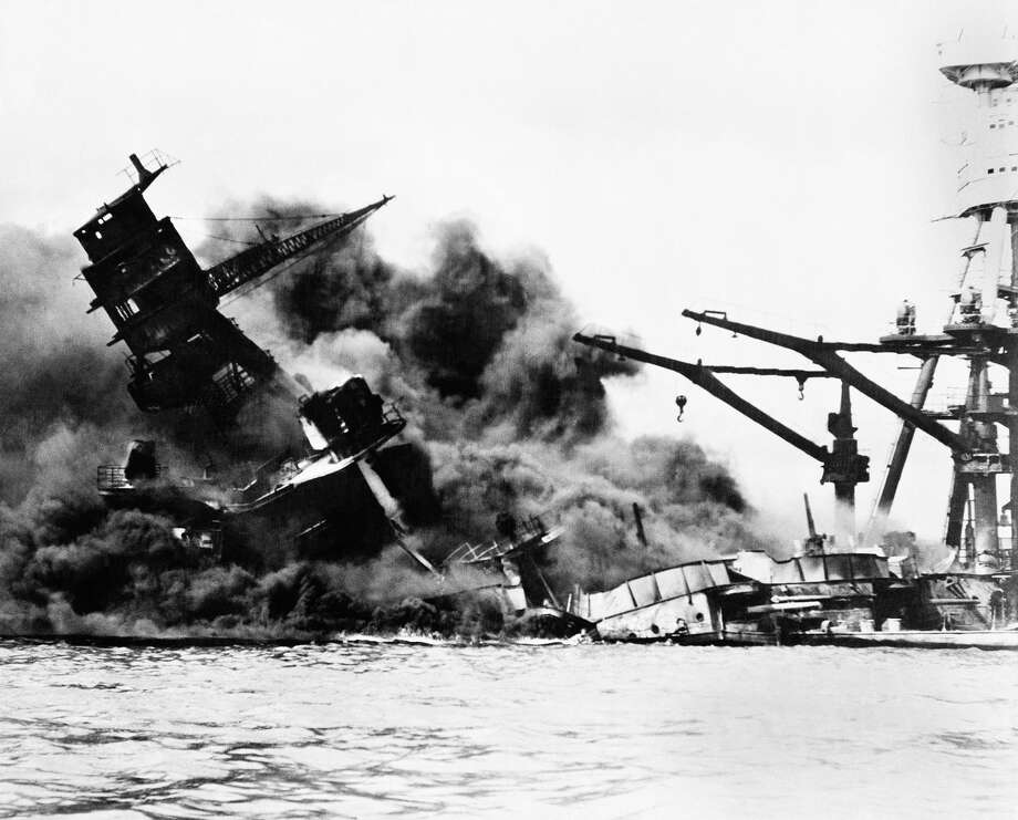 "The battleship USS Arizona belches smoke as it topples over into the sea during Japanese surprise attack on Pearl Harbor, Hawaii, December 7, 1941. The ship sank with more than 80 percent of its 1,500-man crew, including Rear Admiral Issac C. Kidd. The attack, which left 2,343 Americans dead and 916 missing, broke the backbone of the U.S. Pacific Fleet and forced America out of a policy of isolationism. President Franklin D. Roosvelt announced that it was ""a date which will live in infamy"" and Congress declared war on Japan the morning after. This was the first attack on American territory since 1812. (AP Photo) Photo: ASSOCIATED PRESS / AP1941"