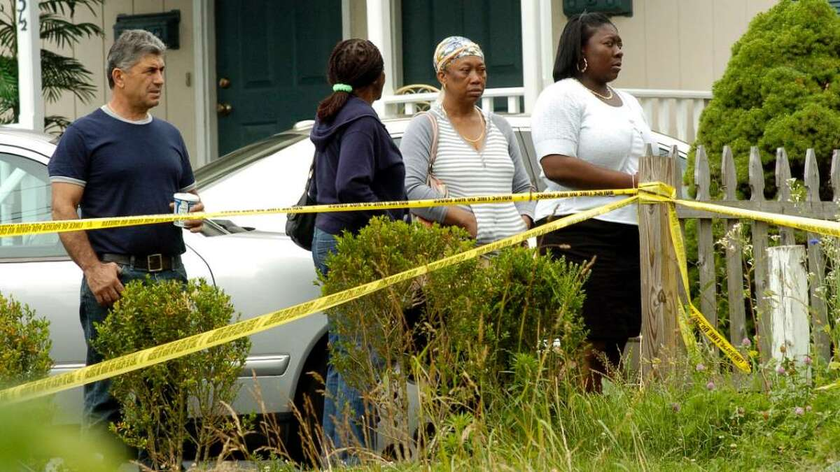 Enid Dickens, 57, and her 73-year-old mother were shot to death this morning June 14, 2010 at their home on 31 Couch Street in Norwalk, Conn. Dicken's ex-husband Gilbert Orlando, 56, was taken into custody in connection with the deaths. Neighbors watch police at the scene.