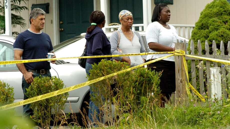 Enid Dickens, 57,  and her 73-year-old mother were shot to death this morning June 14, 2010 at their home on 31 Couch Street in Norwalk, Conn. Dicken's ex-husband Gilbert Orlando, 56, was taken into custody in connection with the deaths. Neighbors watch police at the scene. Photo: Dru Nadler / Stamford Advocate