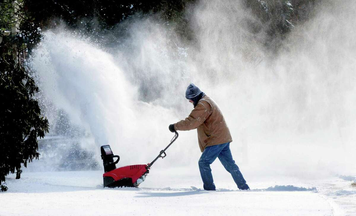 Tom Neznek uses a snow blower to clear snow from the walkway at his house in Milford on 1/3/2014. Photo by Arnold Gold/New Haven Register