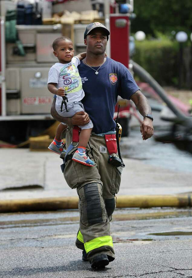 A San Antonio fire fighter carries a child to an waiting bus to be transported to another child care center at the scene of the fire at Bright Kids Daycare Center on Tuesday, Aug. 1, 2017. There were no injuries. Photo: Bob Owen, San Antonio Express-News / ©2017 San Antonio Express-News