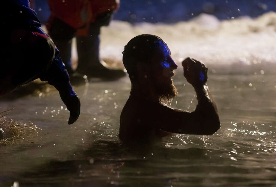 A Russian Orthodox believer swims in the icy water on Epiphany at a pond in Pushkin outside St. Petersburg, Russia, late Saturday, Jan. 18, 2014. The temperature in St. Petersburg is minus 16 Celsius (3.2 Fahrenheit). Thousands of Russian Orthodox Church followers plunged into icy rivers and ponds across the country to mark Epiphany, cleansing themselves with water deemed holy for the day. Water that is blessed by a cleric on Epiphany is considered holy and pure until next year's celebration, and is believed to have special powers of protection and healing. Photo: Dmitry Lovetsky, AP / AP