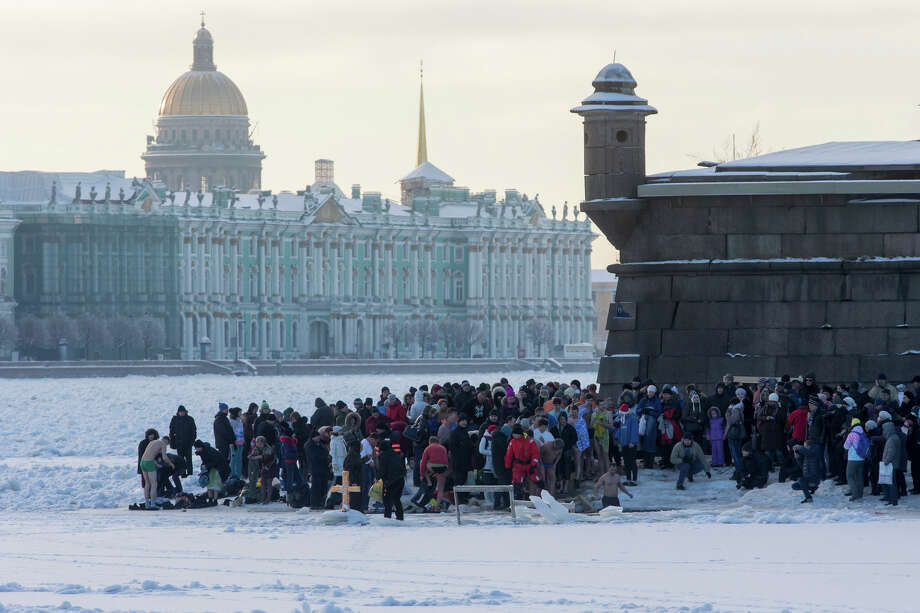 Russian Orthodox believers gather to swim in the icy water on Epiphany in the Neva River in St.Petersburg, Russia, Sunday, Jan. 19, 2014, with Zimny (Winter) Palace in the background. The temperature in St.Petersburg is -16 Celsius ( 3.2  Fahrenhiet). Thousands of Russian Orthodox Church followers plunged into icy rivers and ponds across the country to mark Epiphany, cleansing themselves with water deemed holy for the day. Water that is blessed by a cleric on Epiphany is considered holy and pure until next year's celebration, and is believed to have special powers of protection and healing. (AP Photo/Dmitry Lovetsky) Photo: Dmitry Lovetsky, ASSOCIATED PRESS / AP2014
