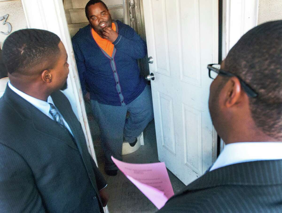 (Melanie Stengel - New Haven Register) Malcolm Welfare (L), Youth Leadership Coordinator for New Haven Public Schools, and Quavon Newton, Youth Minister for Varick Memorial A.M.E. Zion Church (R), give an info packet to Quashon Williams as they canvass the Dixwell area reacing out to disengaged youth 4/9..