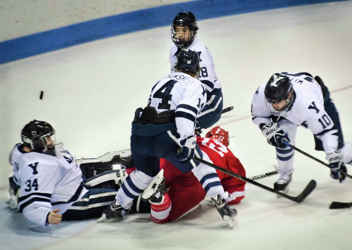 (Melanie Stengel - New Haven Register) Yale goalie, Alex Lyon, is surrounded by teammates Kenny Agostino, Ry Obuchowski, Mitch Witek, and Cornell's John Knisley, in 2nd period action 1/31.