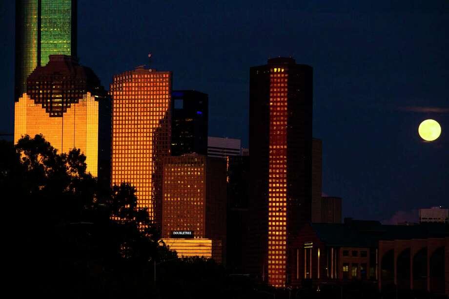 The full moon rises behind the Houston skyline as the sun sets. (Michael Ciaglo / Houston Chronicle ) Photo: Michael Ciaglo, Staff / © 2016  Houston Chronicle