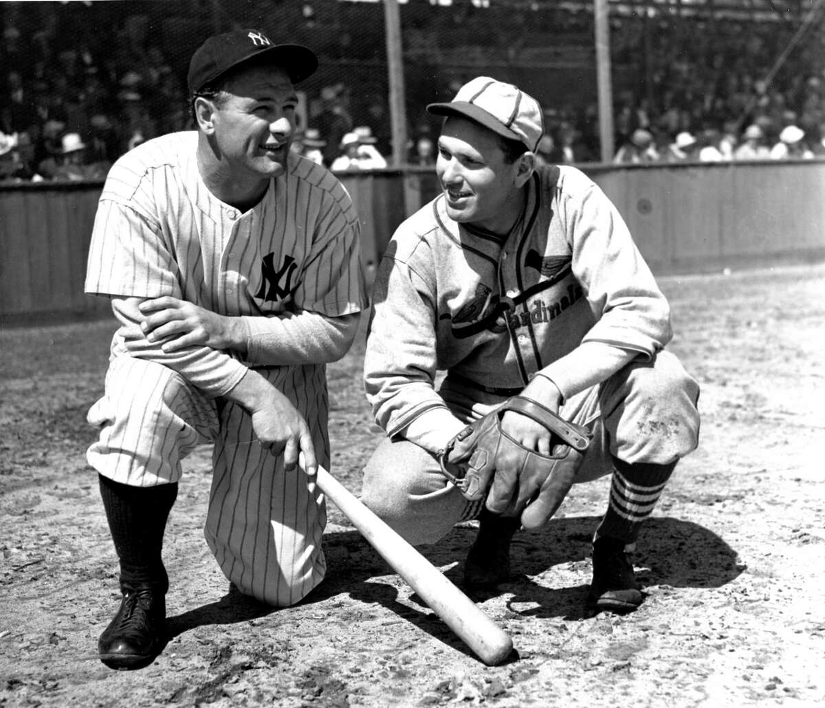 Lou Gehrig, left, of the New York Yankees, and pitcher Dizzy Dean, of the St. Louis Cardinals, compare notes on their 1937 hold-out figures during an exhibition game in St. Petersburg, Fl., April 2, 1937. (AP Photo)