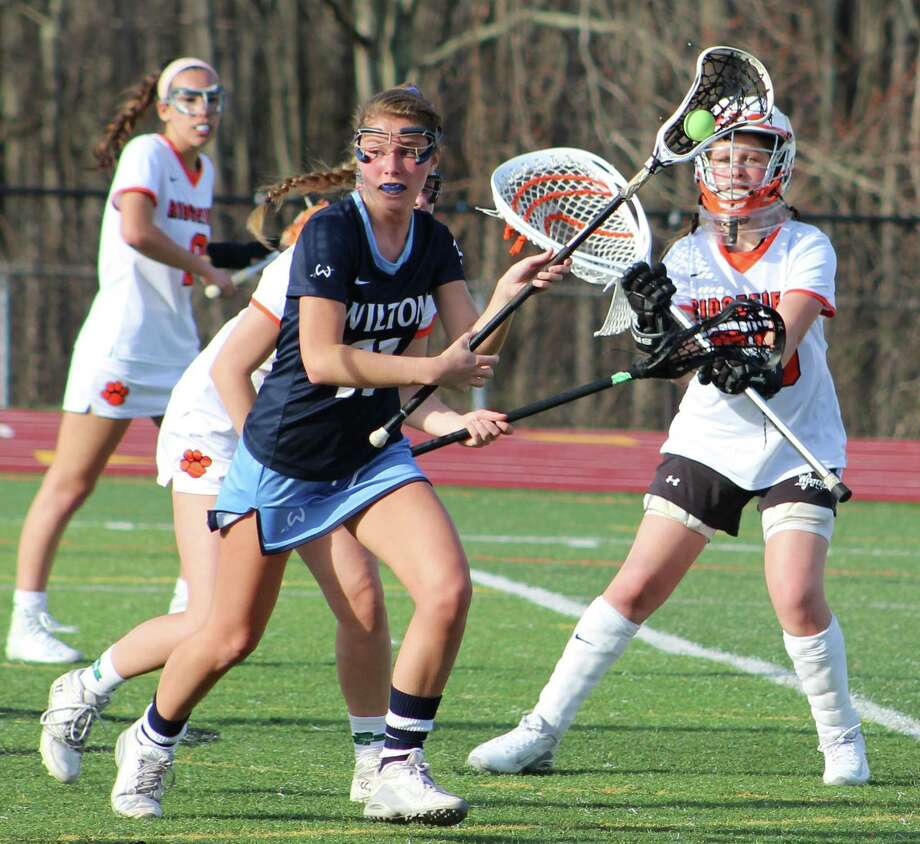 Wilton's Ellie Armstrong looks for an opening as the Ridgefield defense swarms to her during the girls lacrosse game at Ridgefield High School April 11, 2017. Photo: Richard Gregory / Richard Gregory