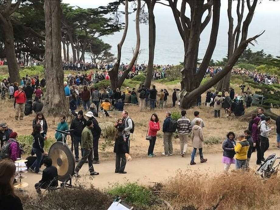 "A crowd gathers on a Lands End hillside to hear John Luther Adams' ""Inuksuit."""