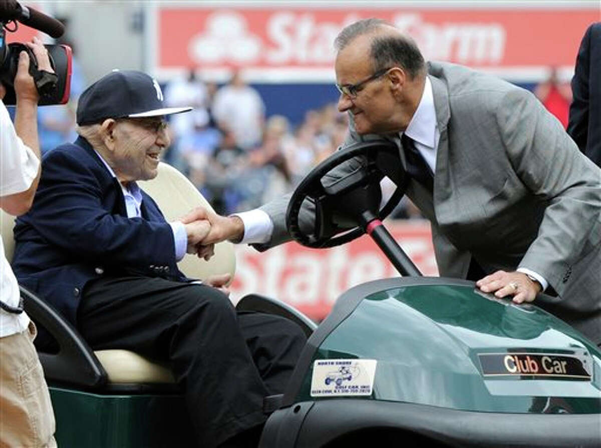 Former New York Yankees manager Joe Torre, right, shake hand with Yogi Berra as the Yankees retired Torre's number before a baseball game against the Chicago White Sox Saturday, Aug. 23, 2014, at Yankee Stadium in New York.