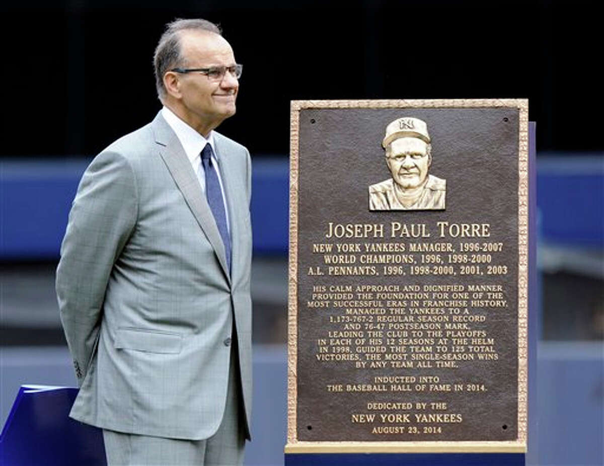 Former New York Yankees manager Joe Torre stands by a replica of his plaque that will hang in Monument Park as the Yankees retired his number before a baseball game against the Chicago White Sox Saturday, Aug. 23, 2014, at Yankee Stadium in New York.