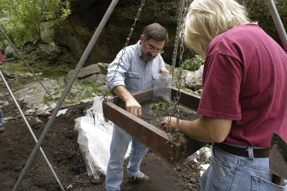 """UTSA researchers Dr. Steve Tomka (background) and Donna Bixby work on a archeolgical dig at Natural Bridge Caverns in 2003. UTSA's Center for Archaeological Research was asked to do the investigation by the owners, the Wuest family, to clear up some of the """"mysteries"""" surrounding the landmark."""