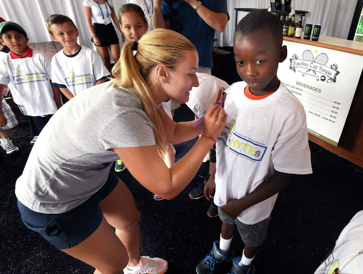 (Mara Lavitt ?' New Haven Register) August 15, 2014 New Haven Today was the first day of the CT Open at the Connecticut Tennis Center. Dominika Cibulkova, the tournament's fifth seed, signs the t-shirt of Martin Duff of New Haven, age 9, a member of New Haven Youth Tennis & Education, or New HYTEs, after the draw ceremony. mlavitt@newhavenregister.com