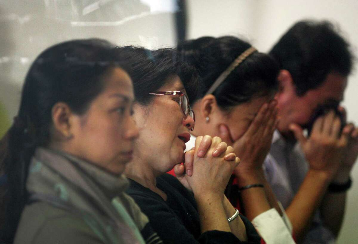 Relatives and next-of-kin of passengers on the AirAsia flight QZ8501 wait for the latest news on the search of the missing jetliner at Juanda International Airport in Surabaya, East Java, Indonesia, Monday, Dec. 29, 2014. Search planes and ships from several countries on Monday were scouring Indonesian waters over which the AirAsia jet disappeared, more than a day into the region's latest aviation mystery. The Flight 8501 vanished Sunday in airspace thick with storm clouds on its way from Surabaya, Indonesia, to Singapore.