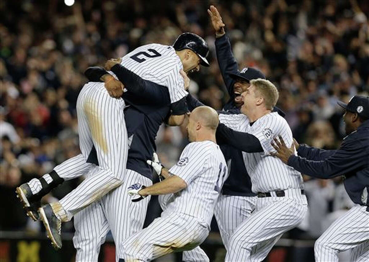 New York Yankees' Derek Jeter (2) is mobbed by teammates after driving in the winning run with a single against the Baltimore Orioles in the ninth inning of a baseball game, Thursday, Sept. 25, 2014, in New York. The Yankees won 6-5.