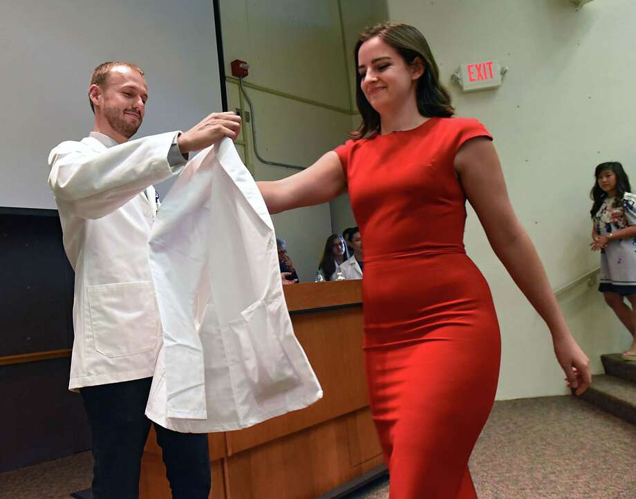 Albany Medical College second year student Christopher Maston of Portland, OR, left, helps incoming medical student Milanka Stevanocic of Clifton Park put on her first white medical coat as AMC holds their White Coat Ceremony on Tues. Aug. 1, 2017 in Albany, N.Y. (Lori Van Buren / Times Union) Photo: Lori Van Buren / 20041166A