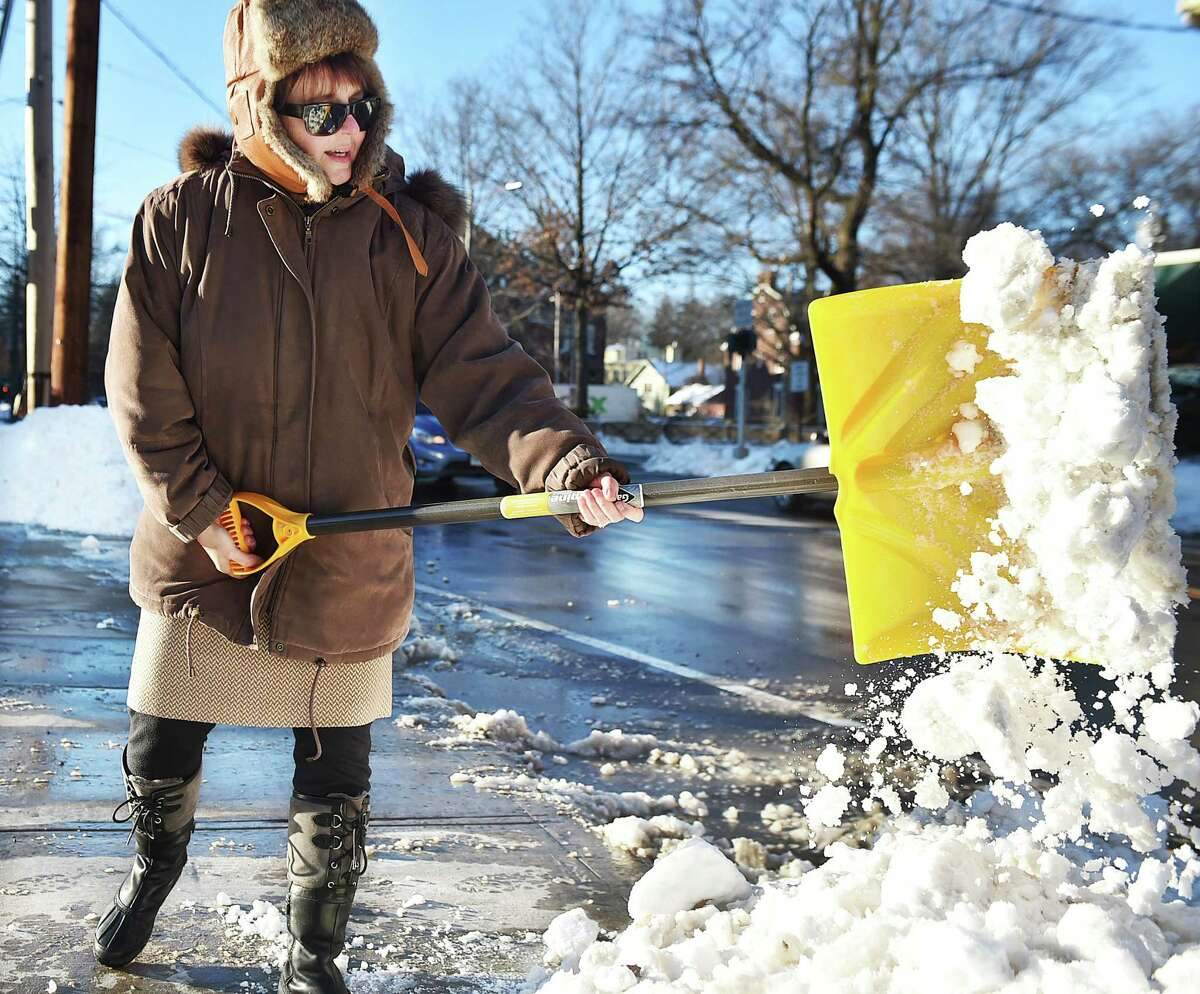 (Catherine Avalone - New Haven Register) Psychologist Debra Boltas, clears snow from the parking lot at her office on Trumbull Street in New Haven Wednesday afternoon, January 28, 2015. Boltas said,