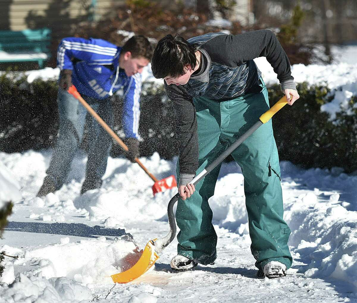 (Catherine Avalone - New Haven Register) Vincent Esposito, 21, front, and Alex Hill, 21, employees of Pasture of Dreams Landscaping in Wallingford clear snow from a driveway on North High Street in East Haven Wedensday, January 28, 2015. Esposito said,
