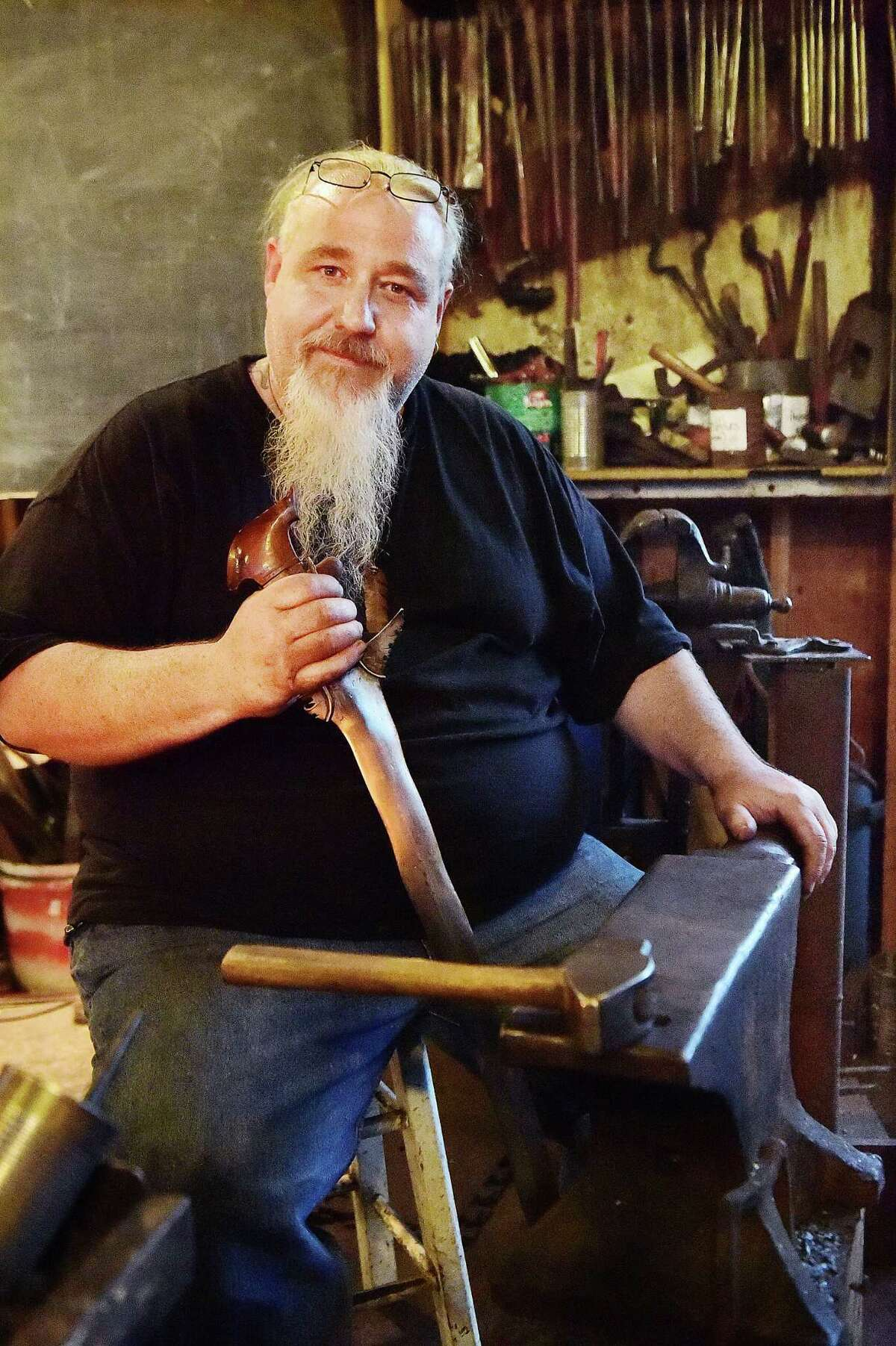Guilford bladesmith Mace Vitale, rated Journeyman smith with the American Bladesmith Society and owner of Laurel Rock Forge , is photographed Wednesday, August 13, 2015, at the Guilford Art Center where he teaches Blacksmithing. Vitale holds an antique Phillipine version of the Kris Sword, similar to the Moro Kris Sword he made when he won the History Channel's Forged in Fire. (Catherine Avalone - New Haven Register)