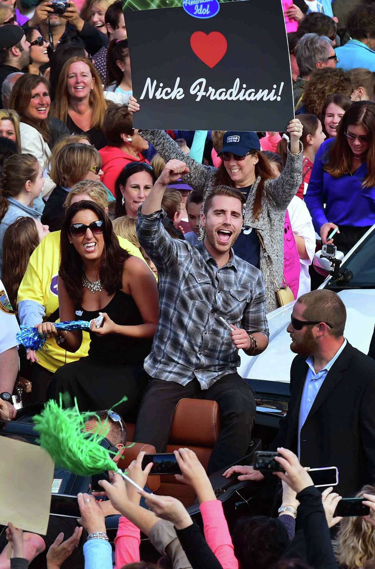 (Peter Hvizdak - New Haven Register) American Idol's Nick Fradiani, of Guilford, gives a fist pump to a familiar face during a welcome home parade on Whitfield Street in Guilford, Connecticut Friday, May 1, 2015.