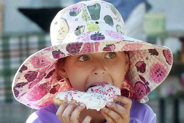 (Melanie Stengel - Register) Connecticut Open Tennis 8/18.Food Court. Lera Strickland, 9, of New Haven, enjoys a square donut from Orangeside Donuts.
