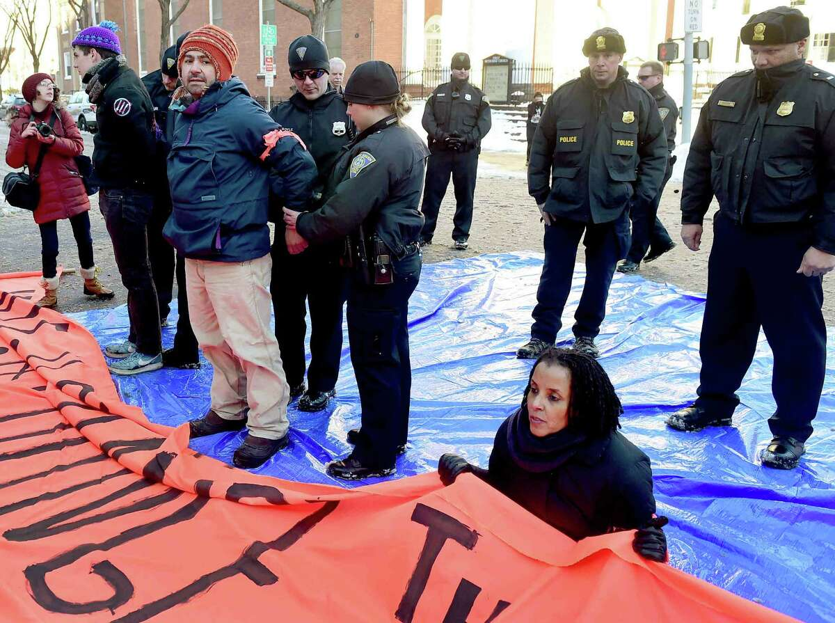 (Peter Hvizdak - New Haven Register) John Lugo of Unidad Latina en Accion of New Haven is arrested during a demonstration after some protestors blocked the intersection of Elm and College Streets in New Haven Friday afternoon, February 10, 2017 and refused to move during a protest in favor of changing the name of Yale University's Calhoun College. The peaceful arrests were pre-planned and coordinated between the demonstrators and New Haven Police.
