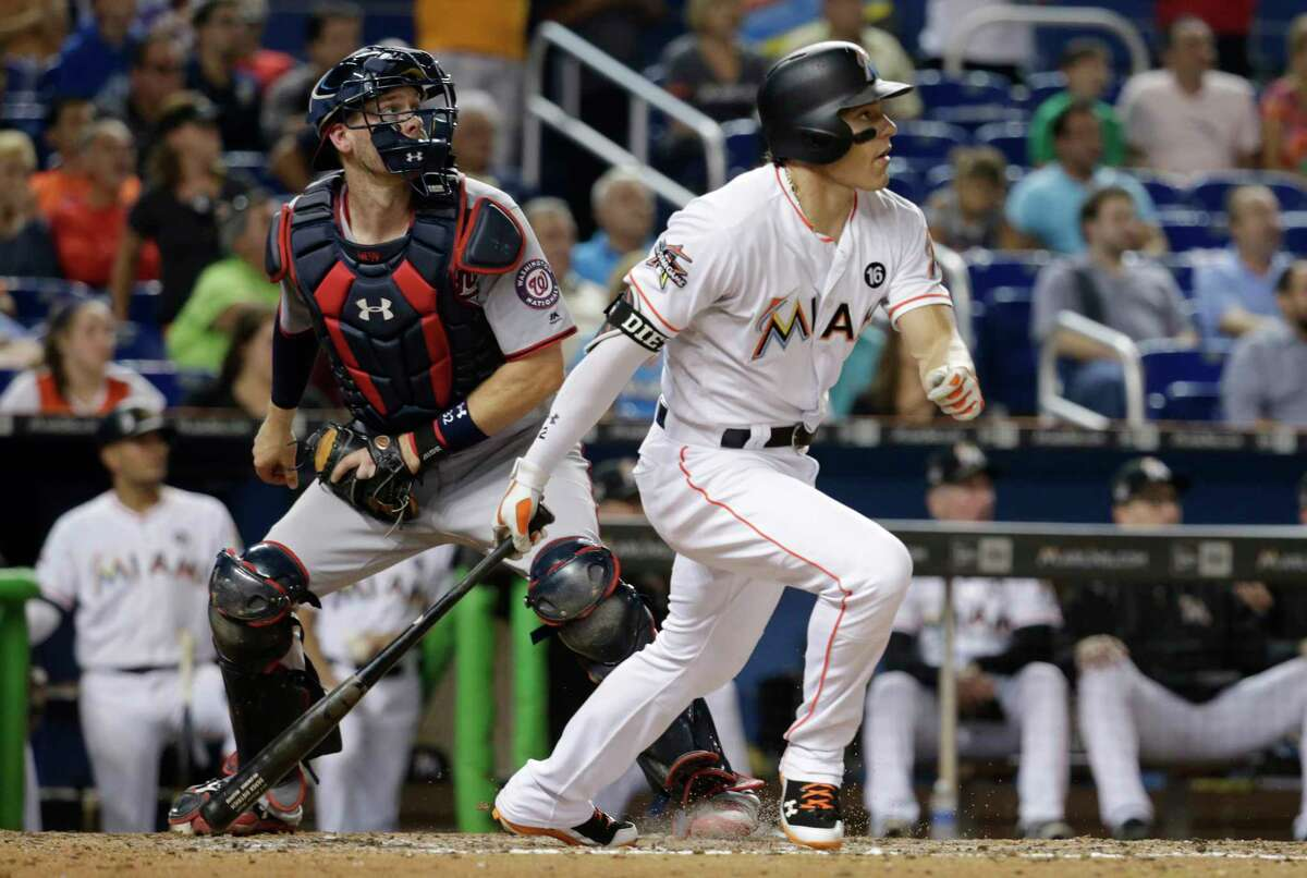 Miami Marlins' Derek Dietrich watches his RBI triple during the fifth inning against the Washington Nationals in a baseball game Tuesday, Aug. 1, 2017, in Miami. At left is Nationals catcher Matt Wieters. (AP Photo/Lynne Sladky) ORG XMIT: FLLS110