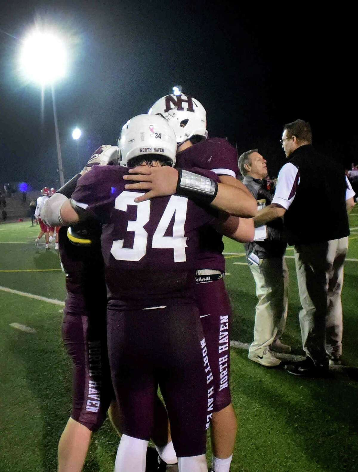 (Peter Hvizdak - New Haven Register) North Haven H.S. head football coach Anthony Sagnella, far right, congratulates New Canaan H.S. head football coach Lou Marinelli second from right, for his Class L state championship game win as North Haven players console each other Saturday, December 12 2015 at West Haven H.S.