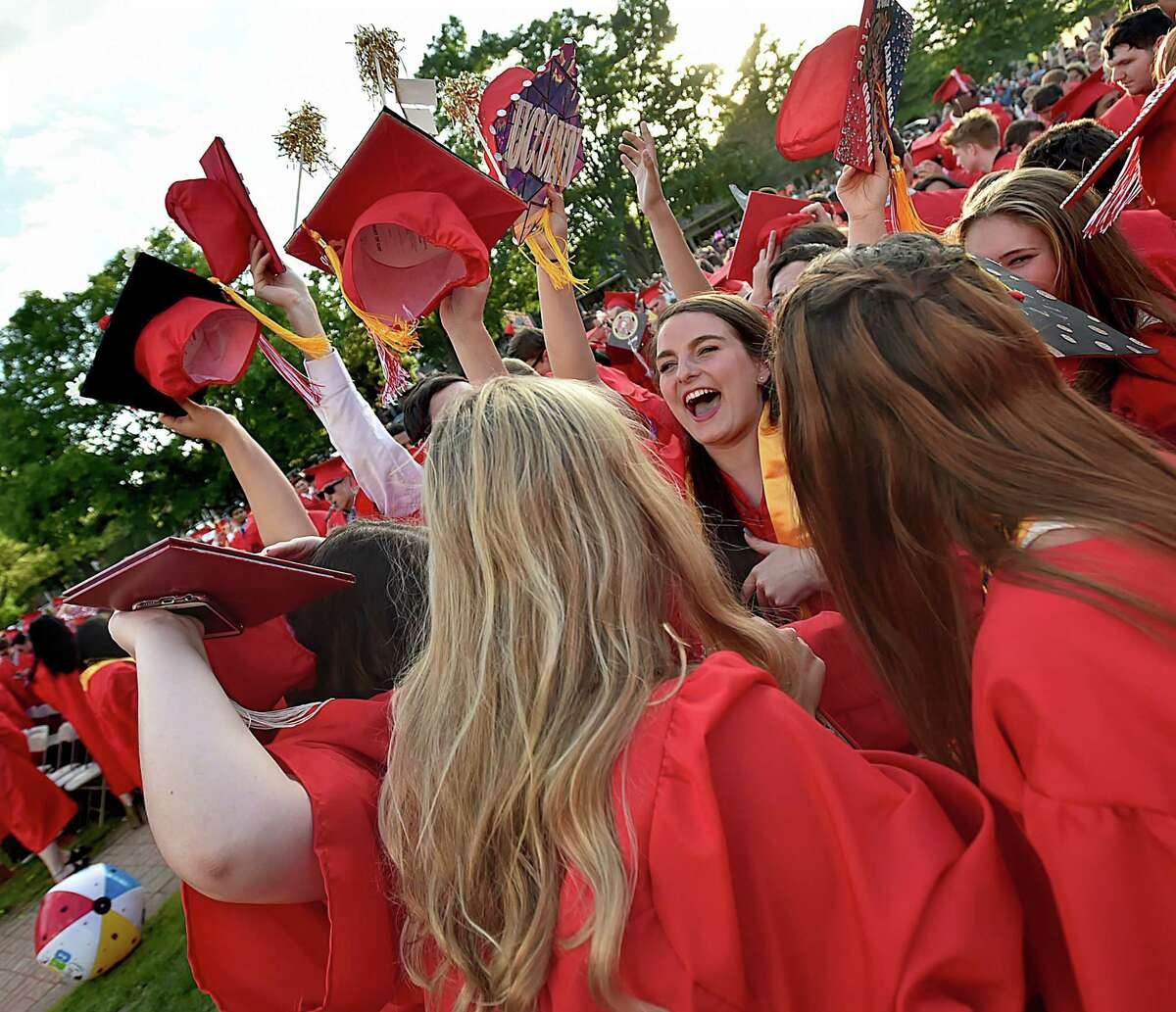 Members of Branford High School's class of 2017 huddle around after tossing their motor boards in the air at commencement exercises, Friday, June 9, 2017, at the Branford Town Green. (Catherine Avalone / Hearst Connecticut Media)