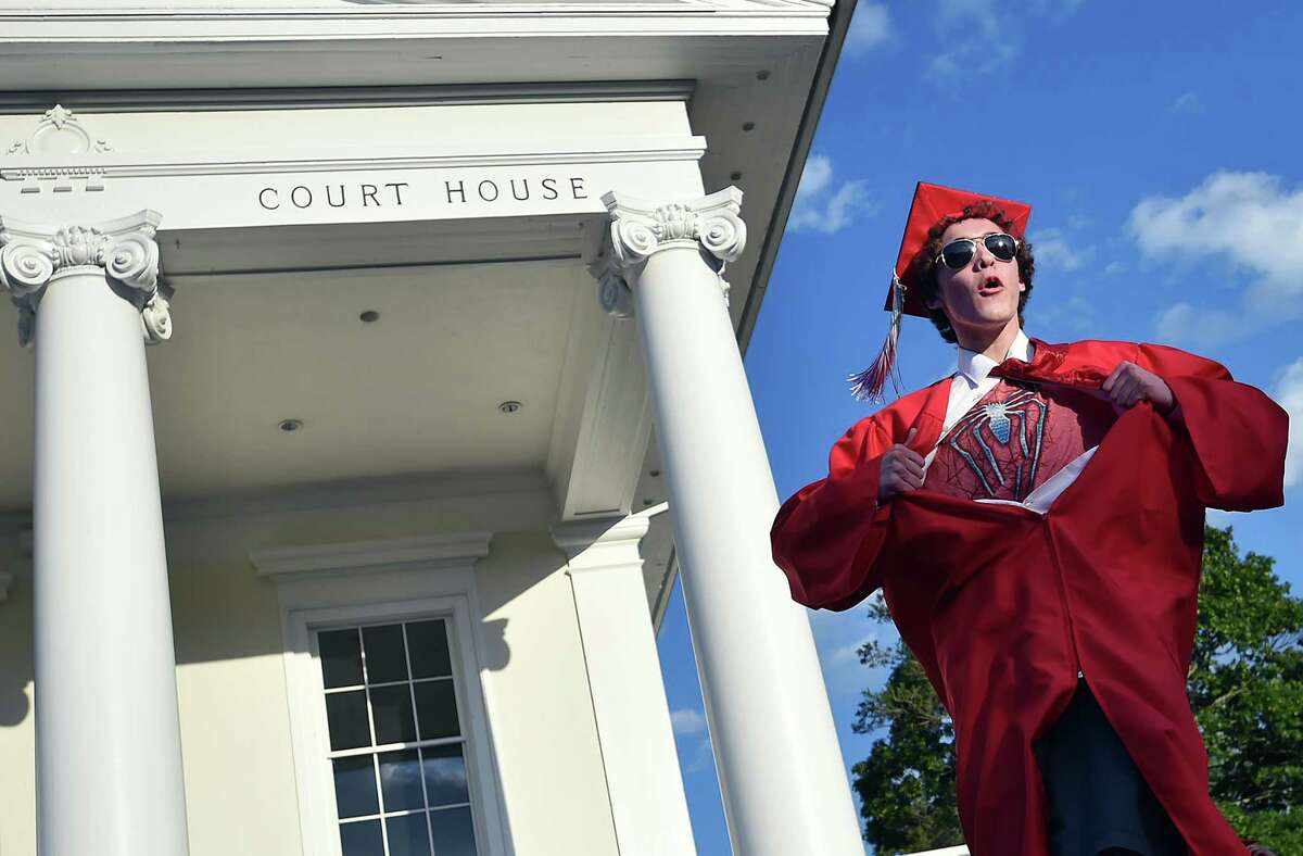Kevin Bartram, a member of Branford High School's class of 2017 rips open his gown and white dress shirt to expose his Spiderman T-shirt just before receiving his diploma commencement exercises, Friday, June 9, 2017, on the Branford Town Green with the courthouse serving as the backdrop. (Catherine Avalone / Hearst Connecticut Media)
