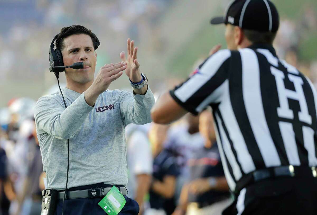 Connecticut head coach Bob Diaco, left, signals for a timeout to an official in the second half of an NCAA college football game against Navy in Annapolis, Md., Saturday, Sept. 10, 2016. Navy won 28-24.