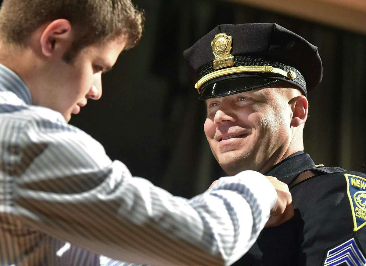 (Catherine Avalone - New Haven Register) Matthew Merced pins a sergeants badge on his father, Det. Alberto Merced during a promotion ceremony held by the New Haven Department of Police Service , Friday, December 5, 2014 at Hill Regional Career High School at 140 Legion Ave. in New Haven. In total, 25 men and women in the department were promoted, five captains, four lieutenants and 16 sergeants including Merced.
