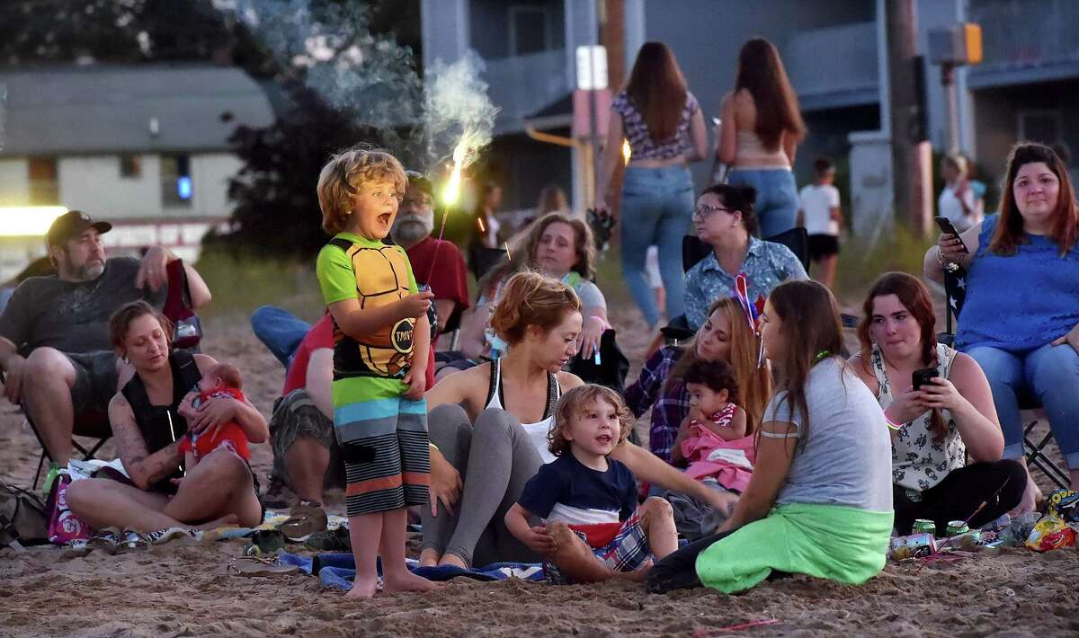 West Haven resident Tristan Portolese, 6, shouts out that a spark from his sparkler burned his hand as he and his family wait on Gull Beach for the West Haven fireworks to start Tuesday, July 5, 2016. The fireworks were postponed from last Friday, July 1, 2016, for inclement weather. (Catherine Avalone/New Haven Register)