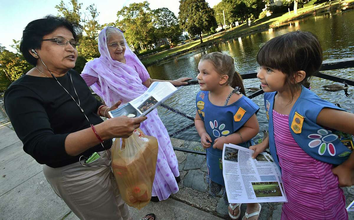 Members of Milford Daisy Scout Troop 30347, Isabelle Phelan, 5, left, and Christina Ann Barbara, 6, spread the word, Wednesday, August 4, 2016, to West Haven residents Usha Jadeja and her mother Mohanba Gohil, about the harm in feeding the waterfowl at the duck pond in Milford. Jadeja and Gohil emigrated from India and were celebrating Shravan Maas, a holy month in their Hindu religion that encourages one to feed the hungry. Phelan and Barbara along with Erynn Willey, 6, Parker Spielman,5, and Abigail Guzas, 6, under direction of Troop Leader Jim Barbara and assistant leader Donna Willey made flyers that are not available at the duck pond behind Milford Town Hall. (Catherine Avalone/New Haven Register)