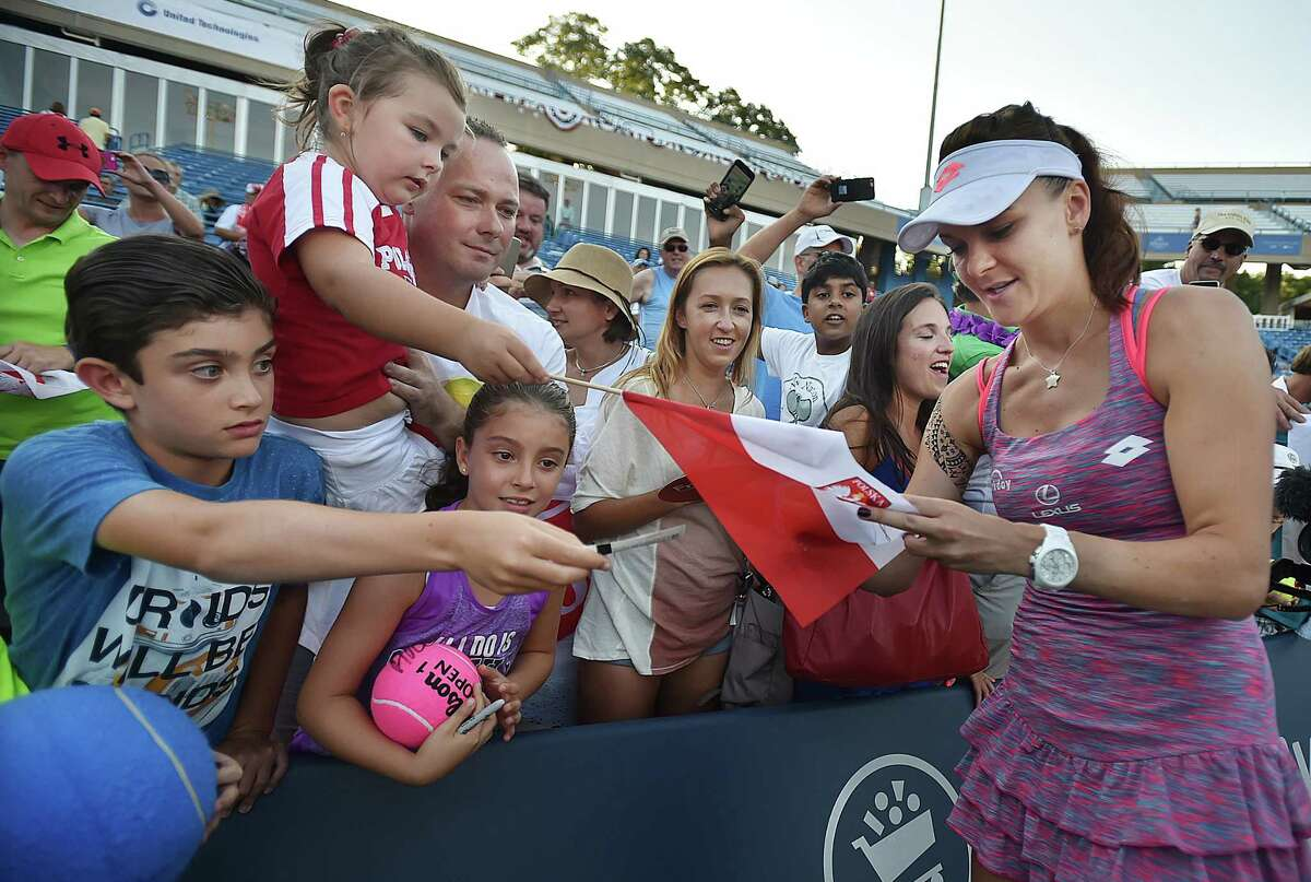 Poland's Agnieszka Radwańska autographs a Polish flag after defeating Ukraine's Elina Svitolina, 6-1 6-1, 7-6 (3) in the championship match at the Connecticut Open, Saturday, August 27, 2016 at the Connecticut Tennis Center in New Haven. (Catherine Avalone/New Haven Register)