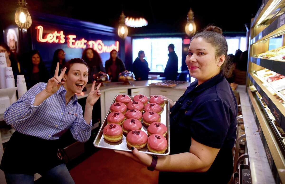 (Peter Hvizdak - New Haven Register) Donut Crazy employees Michaela Murphy, left, and Rita Torres shows of a batch of donuts at the new Donut Crazy donut shop on York Street in New Haven Friday, October 28, 2016.