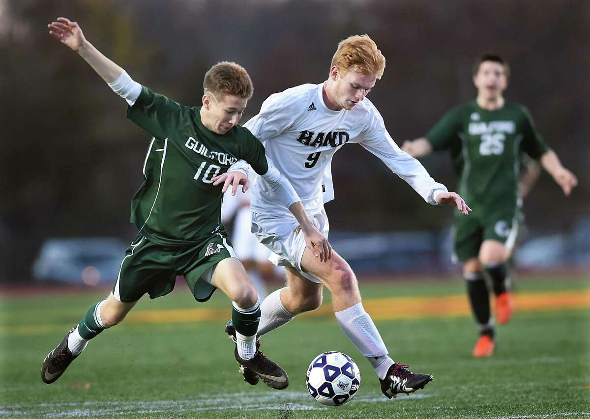 Daniel Hand senior Jake Brown battles Guilford senior Alex Gannon in a 3-0 win for the Tigers, in the CIAC class L soccer semifinals, Wednesday, November 16, 2016, at Willow Brook Park in New Britain. Brown scored the first of Hands three goals in the first half followed by two goals by sophomore Lee Wildermann in the second half. Hand will play Joel Barlow of Redding Saturday, November 19, 2016 at 11 a.m. at Middletown High School. (Catherine Avalone/New Haven Register)